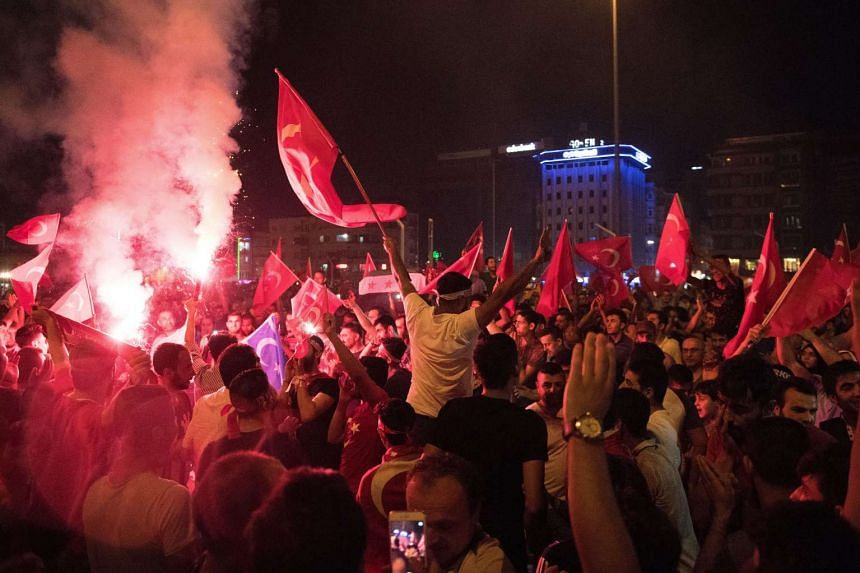 People shout slogans and hold Turkish national flags during a demonstration, against the failed Army coup attempt, at Taksim Sqaure, in Istanbul, Turkey on July 17, 2016.
