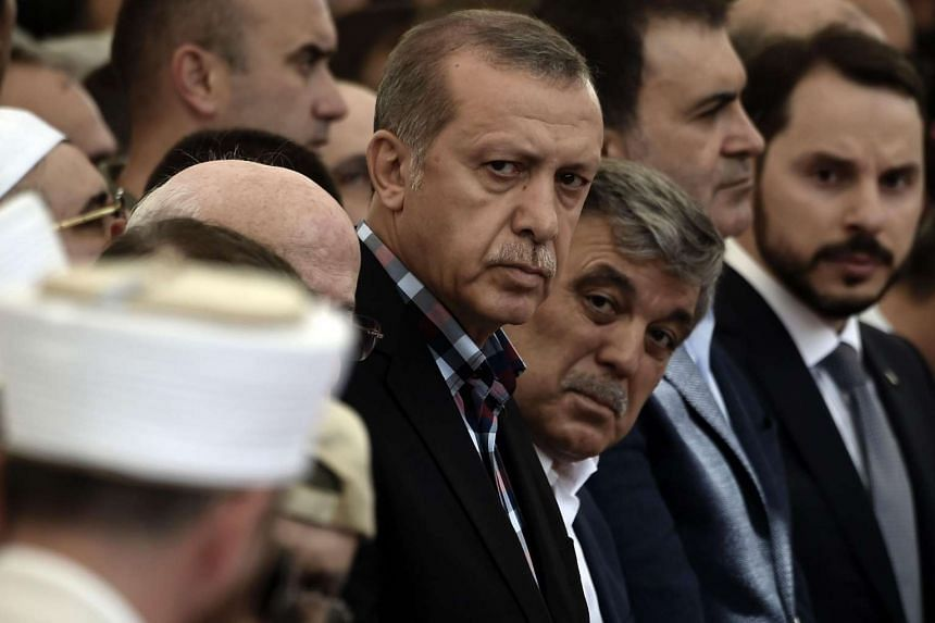 Turkish President Recep Tayyip Erdogan (centre) and former Turkish president Abdullah Gul (centre-right) attend the funeral of a victim of the coup attempt in Istanbul on July 17, 2016.