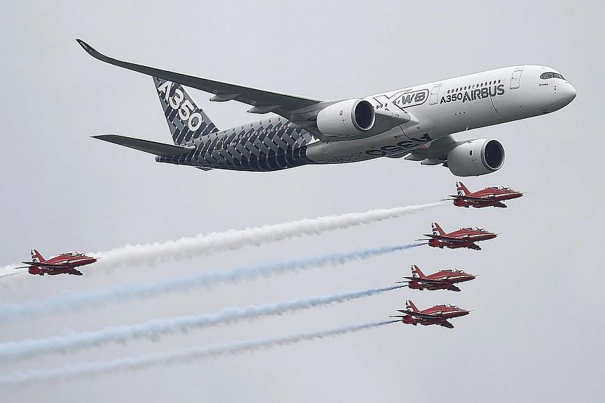 An Airbus A-350 flying with Britain's Red Arrows display team at Farnborough on Friday. The aircraft giant sold 279 planes at the airshow.