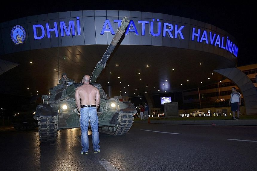 A defiant man standing in front of an army tank at Ataturk airport in Istanbul yesterday as the country came to grips with an attempted coup the day before. People running away on the Bosphorus Bridge during clashes in Istanbul yesterday. There were