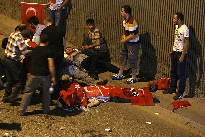 Injured victims being tended to on a street in Ankara yesterday, while a body was draped in the Turkish flag. A confrontation in Taksim Square, Istanbul, yesterday. Less than 12 hours after the coup was attempted on Friday by elements of the military