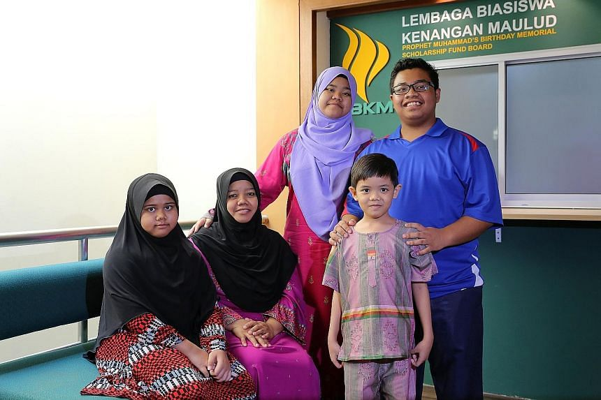 Madam Rohaya (seated, second from left) with her daughters Siti Nur Raudhah (left), 11, and Siti Nur Aisyah, 14, and sons Muhammad Nur Fadhli, 16, and Muhammad Nur Firdhaus, seven. Her husband, the family's main breadwinner, died in a hit-and-run acc