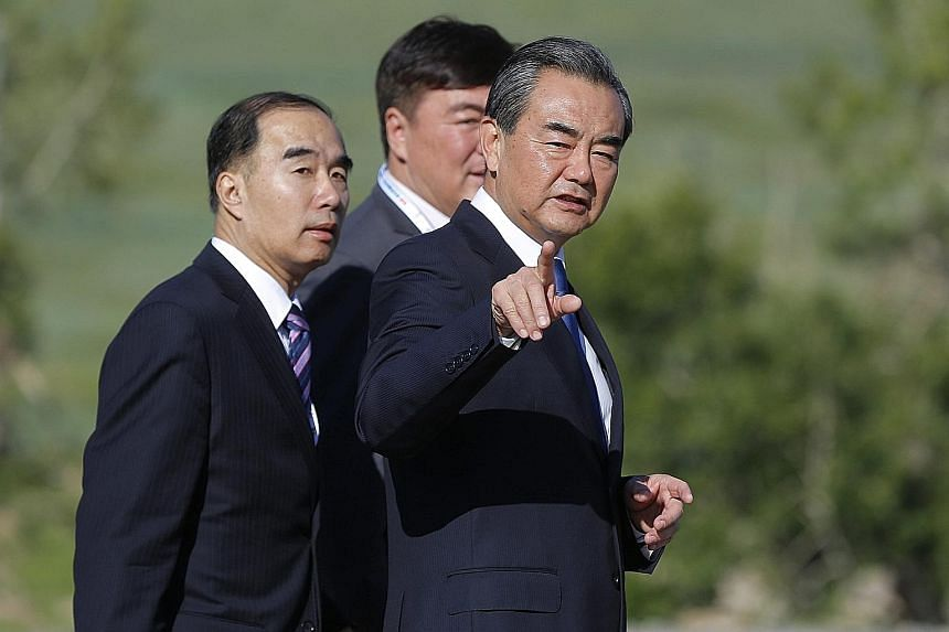 Chinese Foreign Minister Wang Yi (at right) at the Asia-Europe Meeting summit in Ulaanbaatar yesterday. China had asserted that it did not want the South China Sea to be discussed, saying the venue was not appropriate.