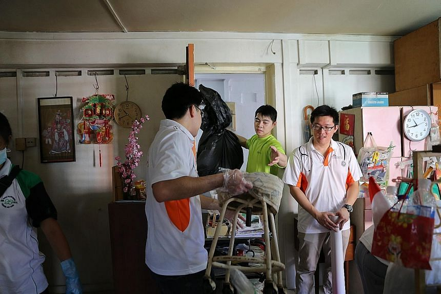 Volunteers moving furniture and trash out of an elderly resident's room to facilitate cleaning. They were part of this year's Project GroomOver, an annual charity drive organised by SGH.