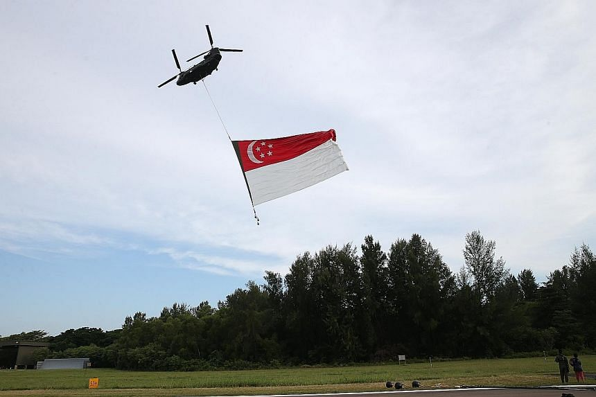Left: The team loads the flag into the helicopter for its move from Pulau Sudong to Sembawang Air Base. Above: The flag will fly past the National Stadium before going across the southern coast.