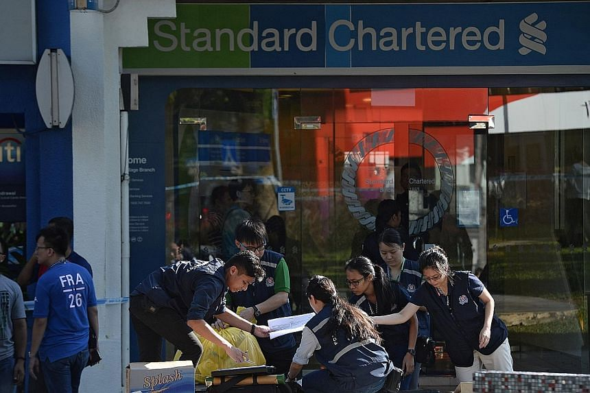 Police and Criminal Investigation Department officers at the Standard Chartered Bank in Holland Village after a robbery there last Thursday. Before investigators could figure out Roach's identity, he had fled Singapore the same day for his next stop