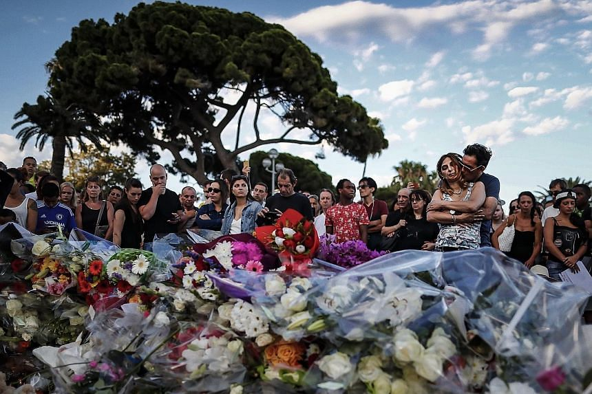 People gathering in front of the memorial set on the Promenade des Anglais where the truck crashed into crowds during the Bastille Day celebrations, in Nice, France, on Friday. At least 84 people died and many were wounded.