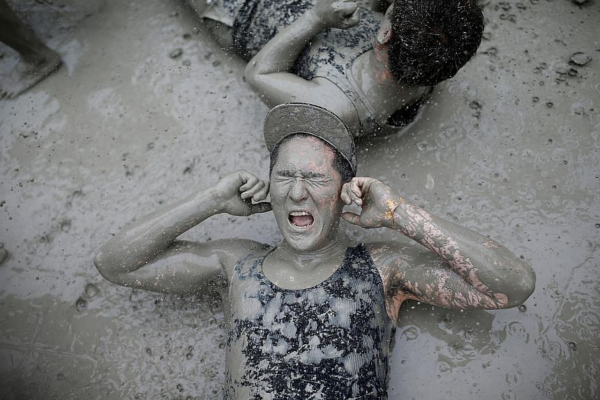 Tourists rolling around in the mud during the Boryeong Mud Festival at Daecheon beach in Boryeong, South Korea, yesterday. The annual festival, which runs from July 15 to 24, aims to encourage the use of mud for cosmetic skincare and promote tourism