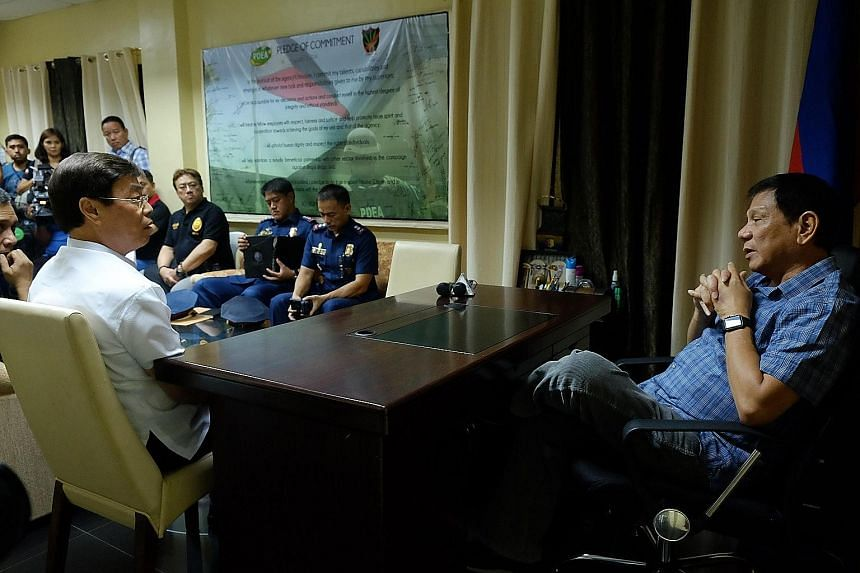 Mr Duterte (right) speaking with Mr Lim during a meeting at the Philippine Drug Enforcement Agency office in Davao. A video of the bizarre meeting was posted on a government YouTube channel yesterday.