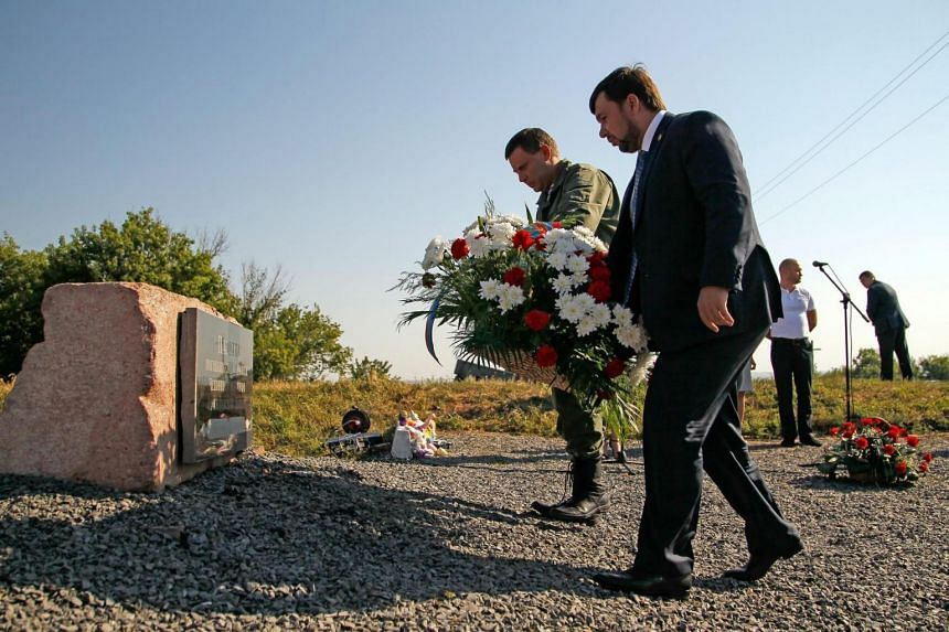 Alexander Zakharchenko (left), leader of self-proclaimed Donetsk People's Republic and Denis Pushilin (right), representative of the DNR place flowers during a mourning ceremony for the victims of the MH17, near the village of Grabovo, Ukraine, on Ju