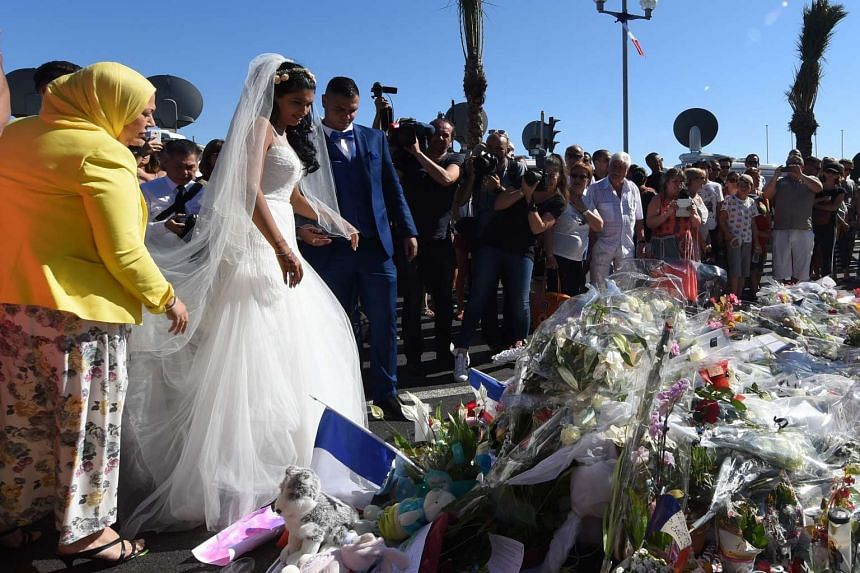 Newly weds lay flowers on the pavement at the Promenade des Anglais in Nice as tribute to the victims of the deadly Bastille Day attack, on July 16, 2016.