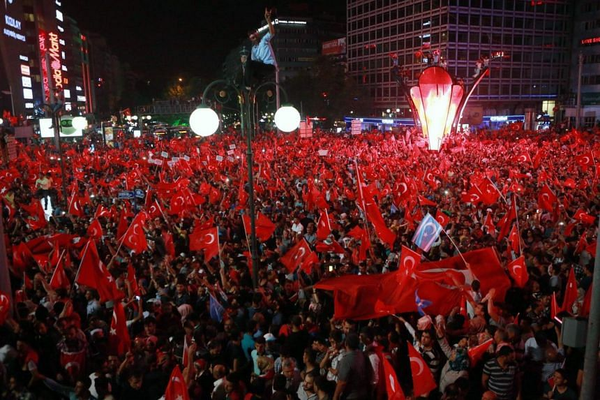 People wave flags as they gather in Kizilay Square in Ankara, during a demonstration in support to the Turkish president.