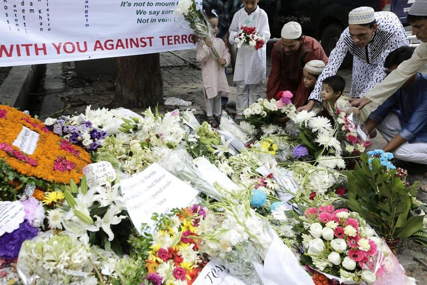 Victims' family members place flowers to pay tribute to the victims of the Dhaka terror attack after Eid al-Fitr prayers on a street near the Holey Artisan Bakery in Dhaka, Bangladesh, July 7.