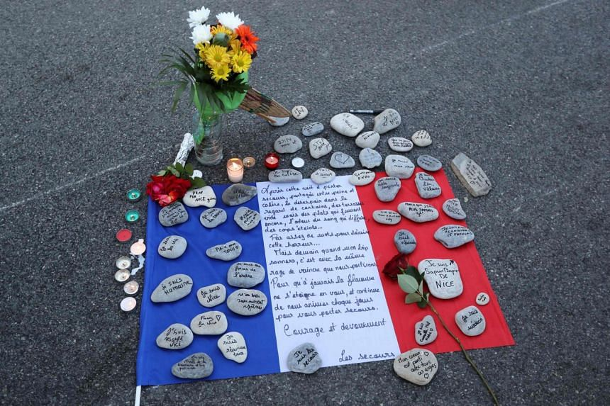 A makeshift memorial made of France's flag and messages written on stones left in the road for victims of the deadly Bastille Day attack.