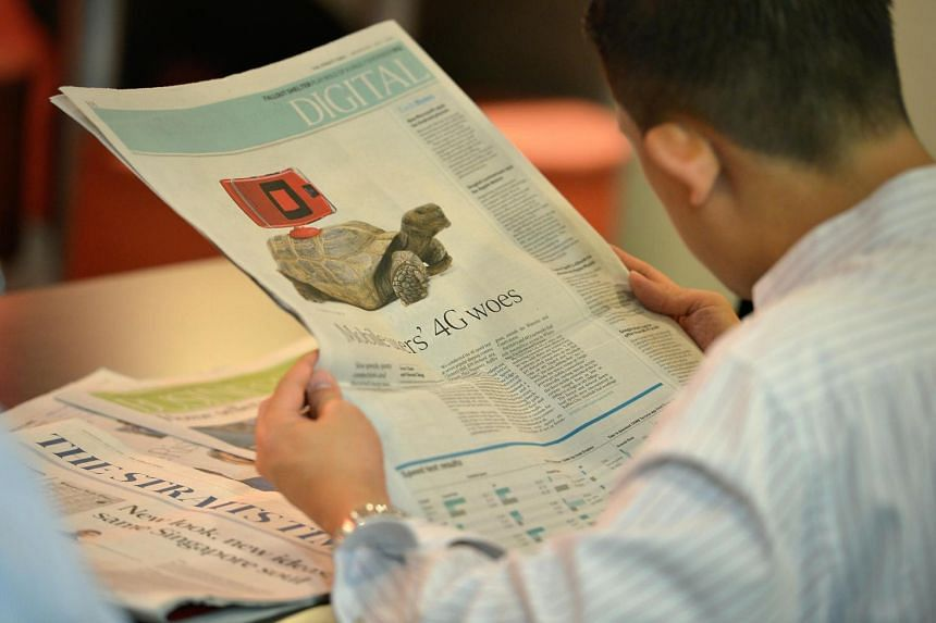 A reader looking at the revamped version of The Straits Times in July 2015 which includes a brand-new layout, typeface and expanded content.