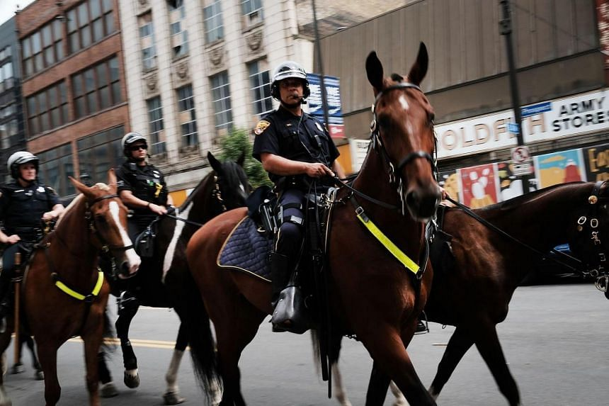 Security personnel on horseback ride through downtown Cleveland on July 16, 2016.