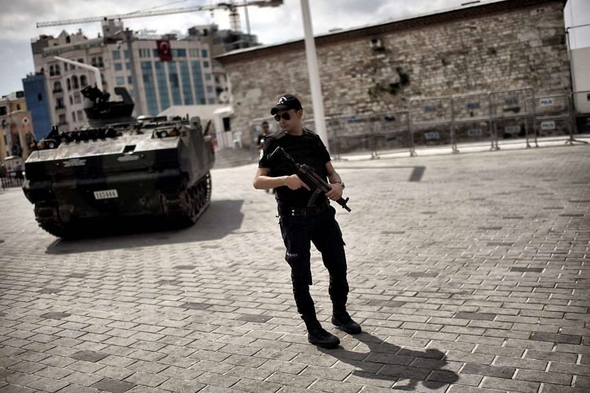 A police officer stands next to an armoured vehicle that was used by soldiers during the coup attempt at Taksim square in Istanbul on July 17, 2016.