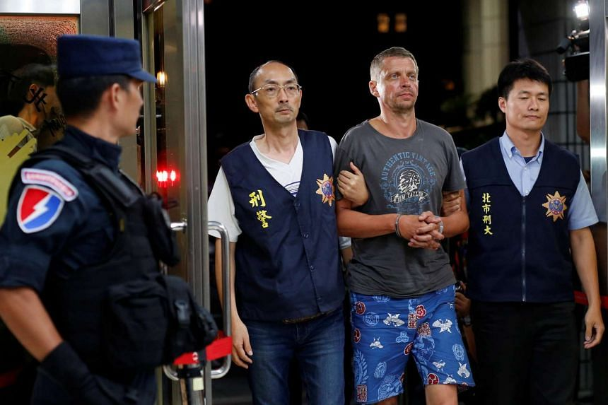 Andrejs Peregudovs from Latvia, who is suspected of stealing from an Automated Teller Machine (ATM), is escorted at the police station in Taipei, Taiwan on July 17.