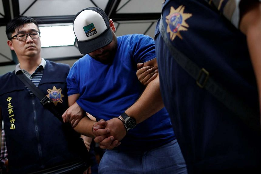 A suspect from Romania, involved in thefts from automated teller machines (ATM), is escorted at the police station in Taipei, Taiwan on July 17.
