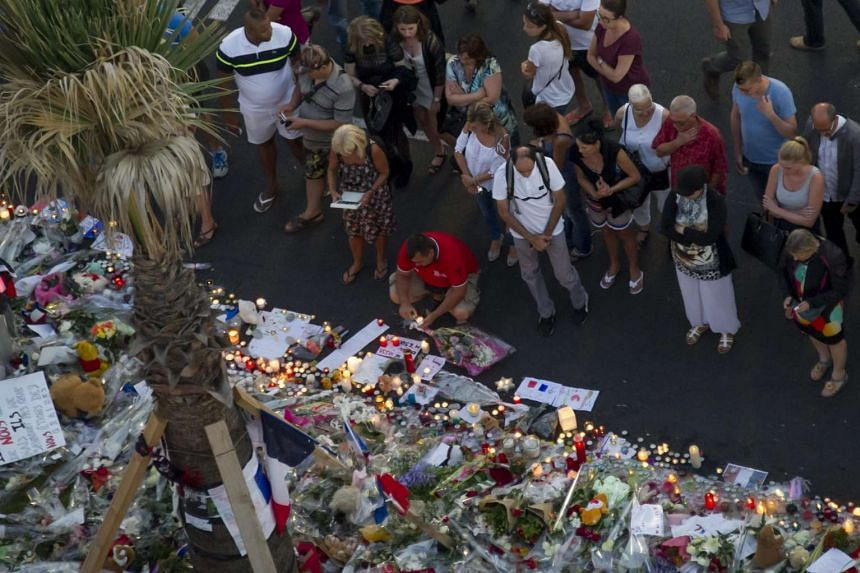 People gather at a makeshift memorial of flowers and candles on the Promenade des Anglais where the truck crashed into the crowd during the Bastille Day celebrations, in Nice, France, July 17.