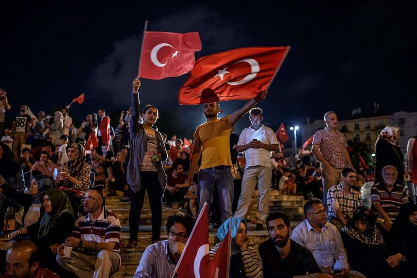 Demonstrators waving Turkish flags at Taksim Square in Istanbul on July 17 during a rally in support of the government following a failed coup attempt.