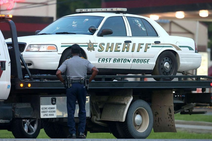A police officer stands in front of an East Baton Rouge police car with bullet holes as it's towed away from the scene where three police officers were killed on July 17 in Baton Rouge, Louisiana.