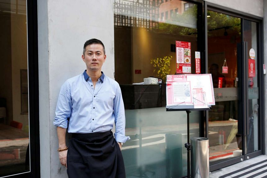Chris Lee, a migrant from Hong Kong, poses at his restaurant in Taipei, Taiwan on July 15.