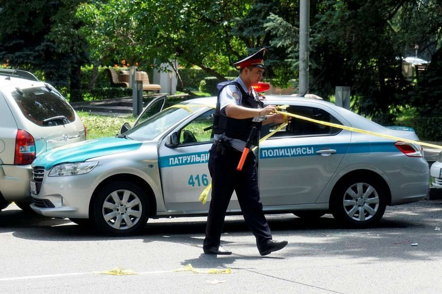 A police officer wraps up police tape at a street in Almaty, Kazakhstan, on July 18, 2016.