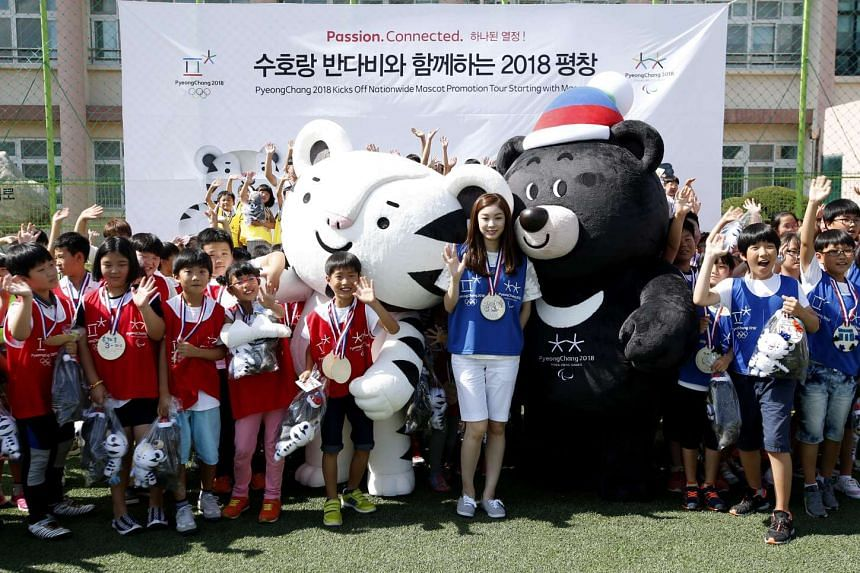 The 2018 Pyeongchang Winter Olympics Mascots Soohorang (centre-left) and Bandabi (centre-right) with former South Korean figure skater Kim Yu Na (centre) and children in Pyeongchang on July 18, 2016.