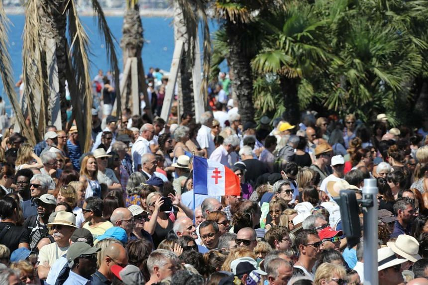 A man holds a French flag showing the Cross of Lorraine as people gather to observe a minute of silence for the victims of the Bastille Day attack on the Promenade des Anglais in Nice on July 18, 2016.