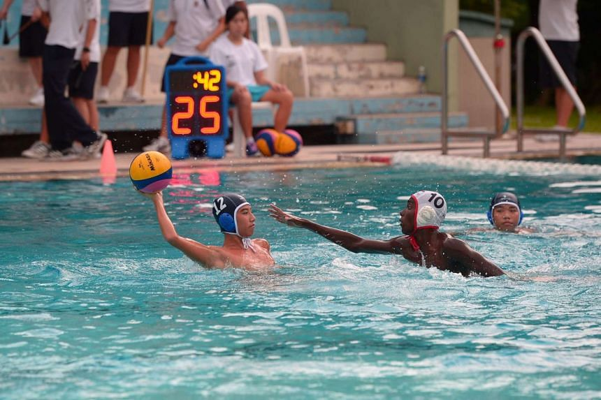 Hwa Chong Institution's Abel Tan (left) passes the ball forward, while ACS(I)'s Vicknessh s/o Mathiwanen  tackles during their National water polo C division final match on July 18, 2016.
