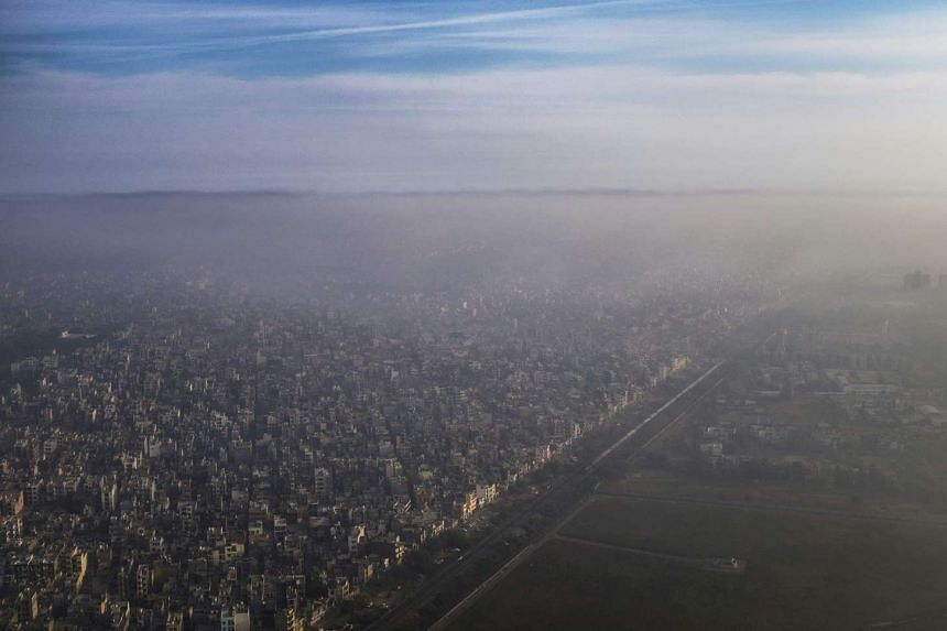 A blanket of smog extends over a densely populated neighbourhood adjacent to the main airport in New Delhi, on March 15, 2016.