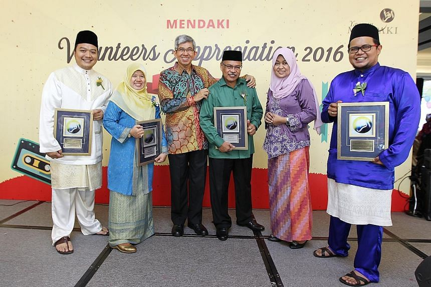 Dr Yaacob (third from left) and Yayasan Mendaki CEO Tuminah Sapawi (fifth from left) with some of the award winners yesterday. They are (from left) Mr Muhammad (outstanding volunteer award), Madam Wahizah (long-service award), Haji Salim Suri (senior