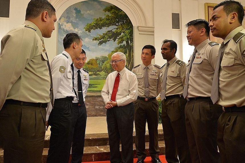 President Tony Tan Keng Yam, accompanied by Chief of Defence Force Lieutenant-General Perry Lim (fourth from right), talking to operationally ready national servicemen (from left) Major (NS) Adam Assik Shahrir, Corporal First Class (NS) Wong Liang Ch