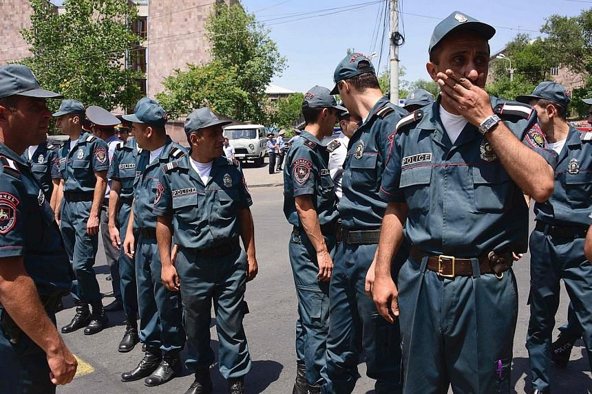 Armenian police officers blocking the streets to Erebuni police station in Yerevan yesterday. One policeman was killed and several were taken hostage when an armed Armenian group with links to a jailed opposition leader seized a police building.