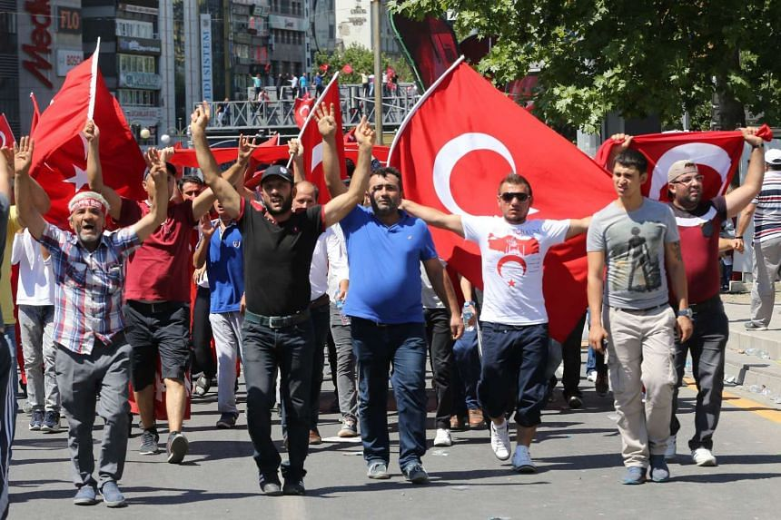 People waving national flags as they march from Kizilay square to the Turkish General Staff building, following a failed military coup attempt, in Ankara on July 16, 2016.