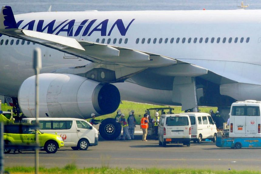 Officials changing a tyre of an Hawaiian Airlines plane after it made an emergency landing at Haneda airport in Tokyo on July 18.