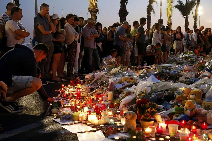 People gather around flowers and burning candles to pay tribute to victims of the Bastille attack in Nice, France on July 17.