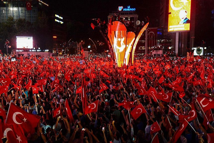Pro-Erdogan supporters wave Turkish flags at Kizilay square in Ankara on July 18 during a demonstration in support to the Turkish government following a failed coup attempt.