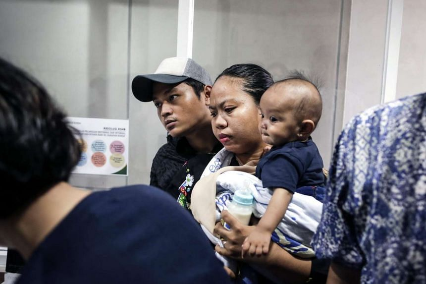 Indonesian parents gather as they check their kids' vaccination details at a protest against fake vaccines at a hospital in Jakarta, on July 15, 2016.