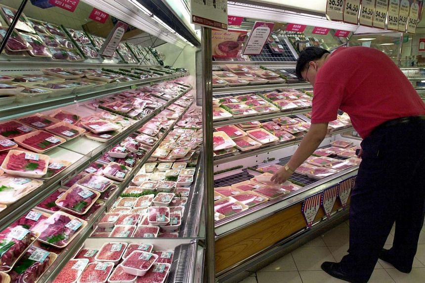 A consumer browsing the red meat section at a supermarket in Japan.