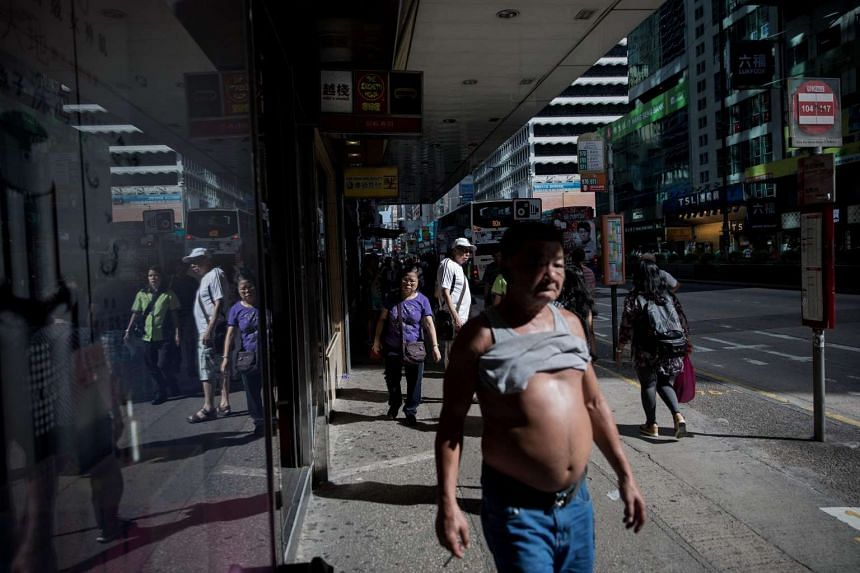 People walk along a street on a hot day in Hong Kong on June 26.