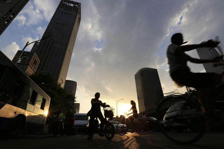 Cyclists silhouetted during sunset in the Central Business Distrct of Beijing, China, July 1.