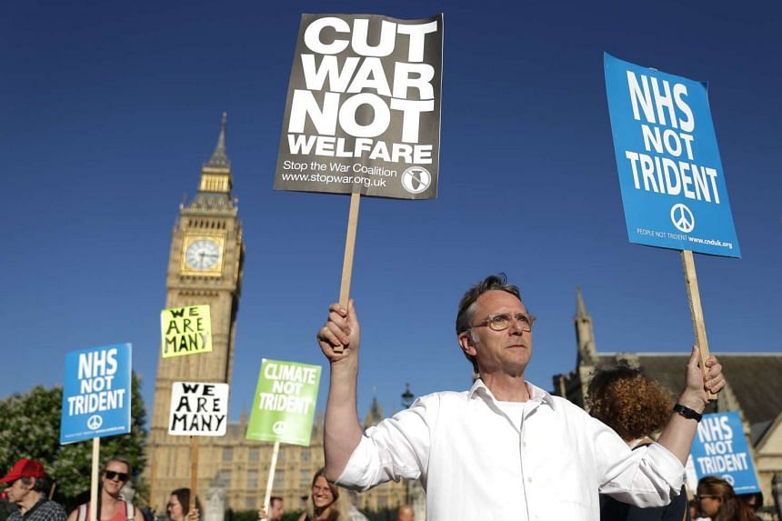 Demonstrators hold placards as they attend an anti-war and anti-trident demonstration near the Houses of Parliament in central London on July 18, 2016.