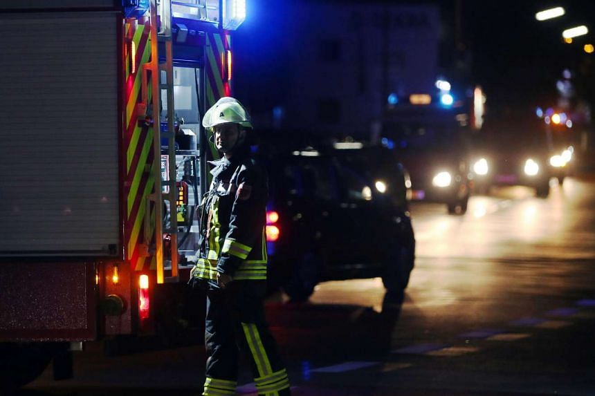 A rescuer stands on a road near railtracks in Wuerzburg, Germany, after a man attacked train passengers with an axe.