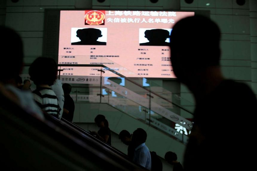 People riding on escalators seen passing an electronic screen showing information of runaway debtors at Shanghai railway station in Shanghai, China, July 15.