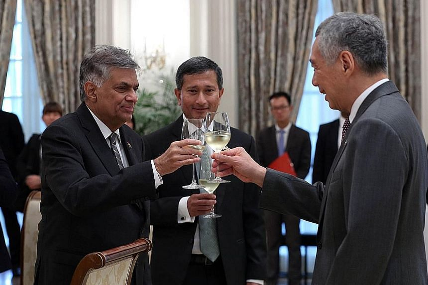 PM Lee and Mr Wickremesinghe toasting each other at the Istana yesterday, with Foreign Minister Vivian Balakrishnan looking on. PM Lee said that when the Singapore-Sri Lanka free trade agreement is completed, it will be a boost for companies and inve