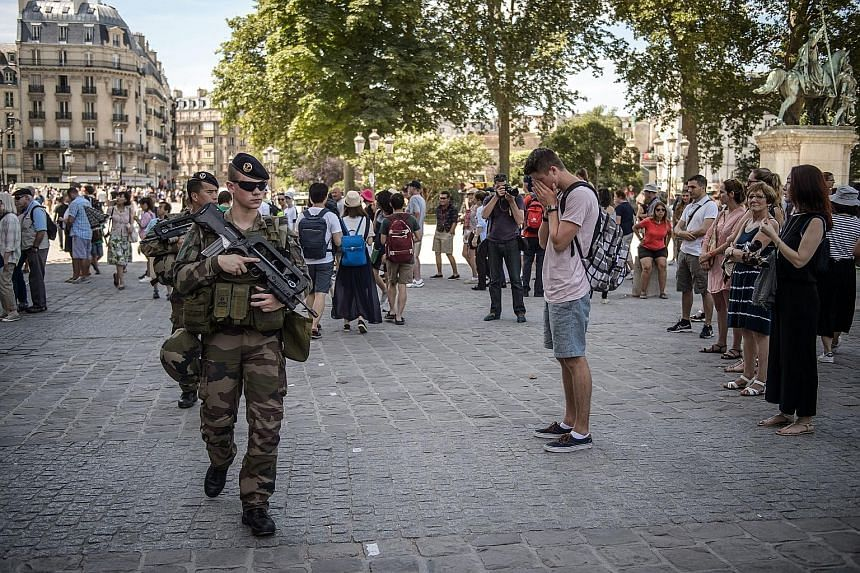 French soldiers on patrol in front of the Notre Dame Cathedral in Paris as the country observed a minute of silence yesterday for the victims of last Thursday's attack in Nice. The attacker, Bouhlel, used a truck to mow down people along Nice's seasi