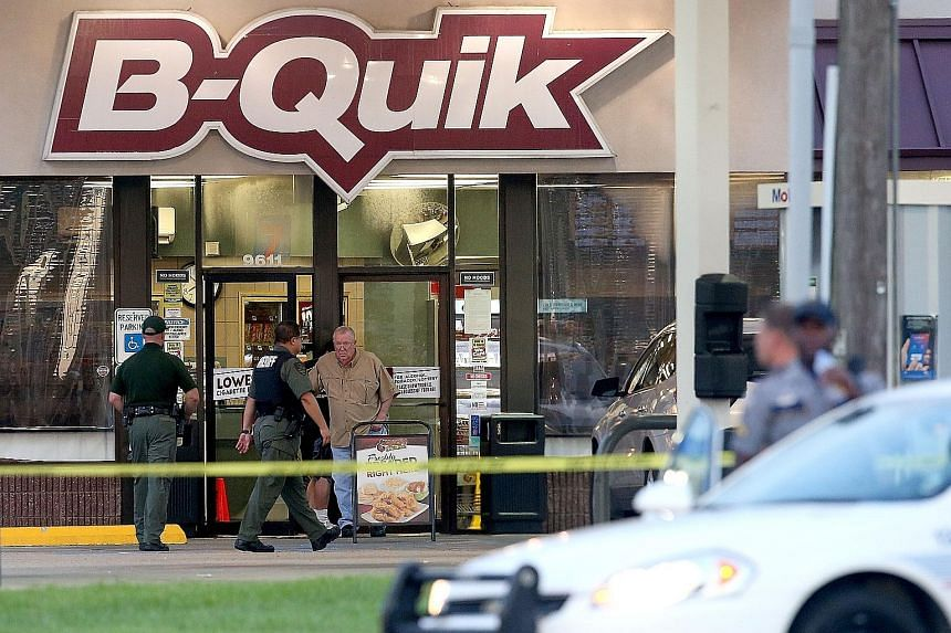 The scene of the shoot-out on Sunday where three police officers were killed by a former US Marine sergeant. Several officers came under fire as police responded to a 911 emergency call about a man dressed in black standing behind a store holding a r