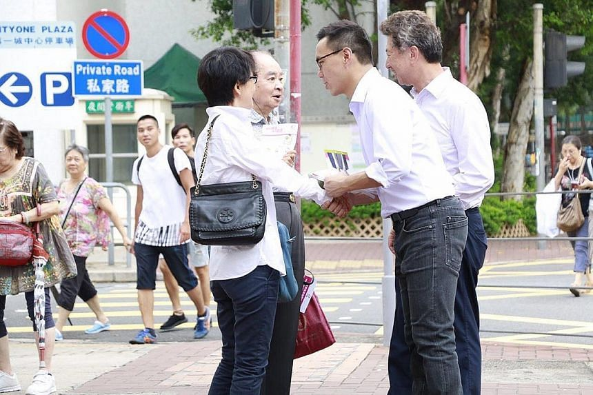 Pan-democrats Ronny Tong (far right) and candidate Raymond Mak campaigning in Sha Tin.
